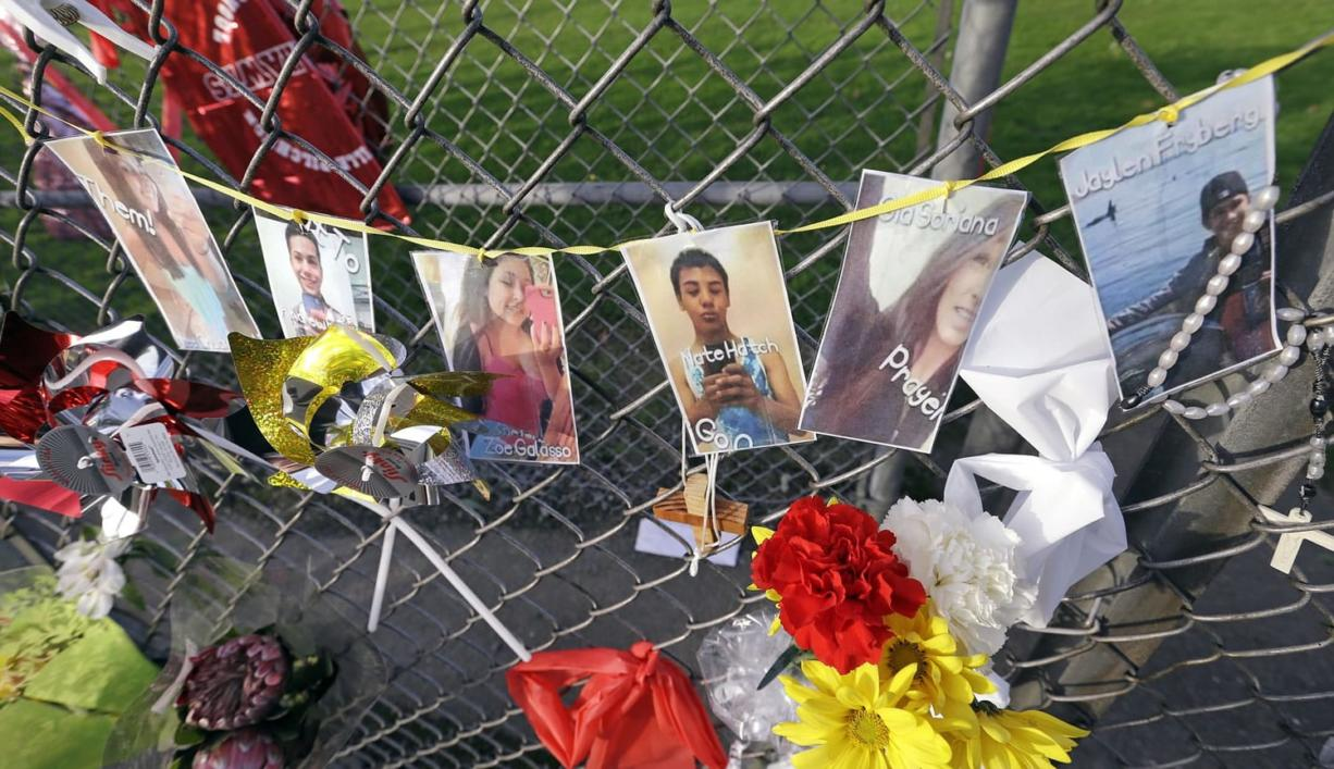 Photos of students shot, and the shooter, are hung together on a fence at Marysville-Pilchuck High School memorializing a shooting there last week, Wednesday in Marysville. Teacher Megan Silberberger who tried to intervene to stop the school shooting there last week says she reacted just as any of her colleagues would have.