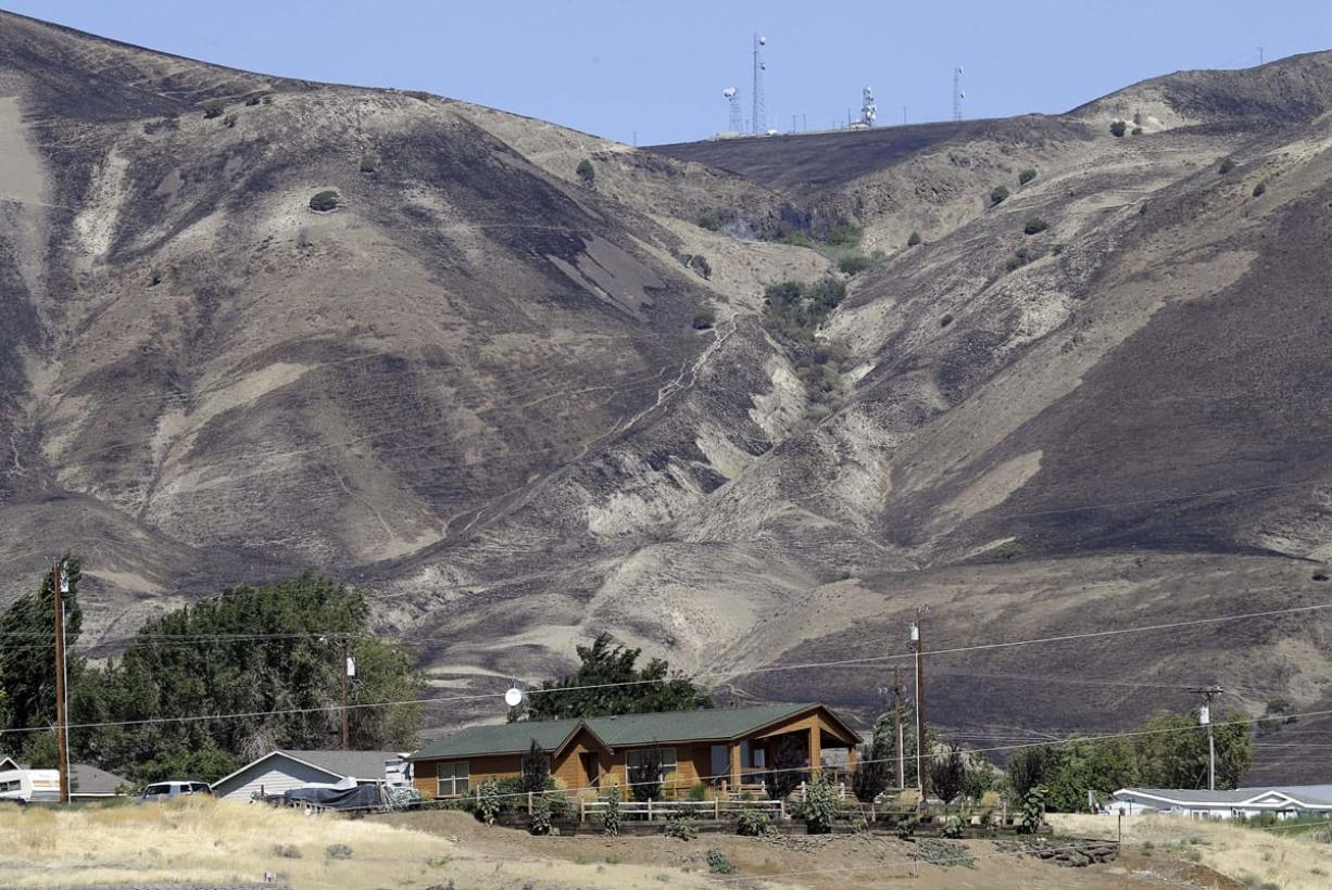 Fire-blackened hills above a residence in Roosevelt, Wash., shows how close an early morning wildfire came to the town, Wednesday, Aug. 5, 2015.   Residents, who evacuated overnight, have returned to their homes and the fire is headed away for the town.