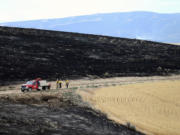 Three Chewack Fire Suppression workers stand Sunday near ground burned by the Douglas County Complex Fire near Waterville.