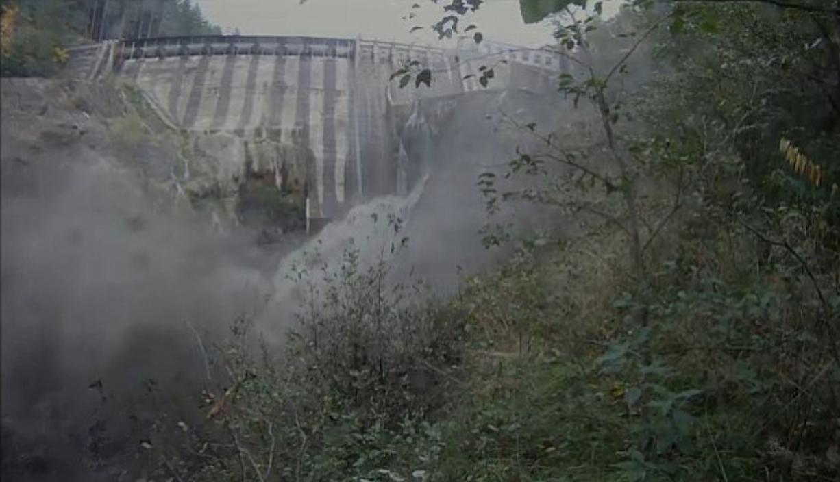 A torrent of water issues from the breached Condit Dam moments after the initial blast.