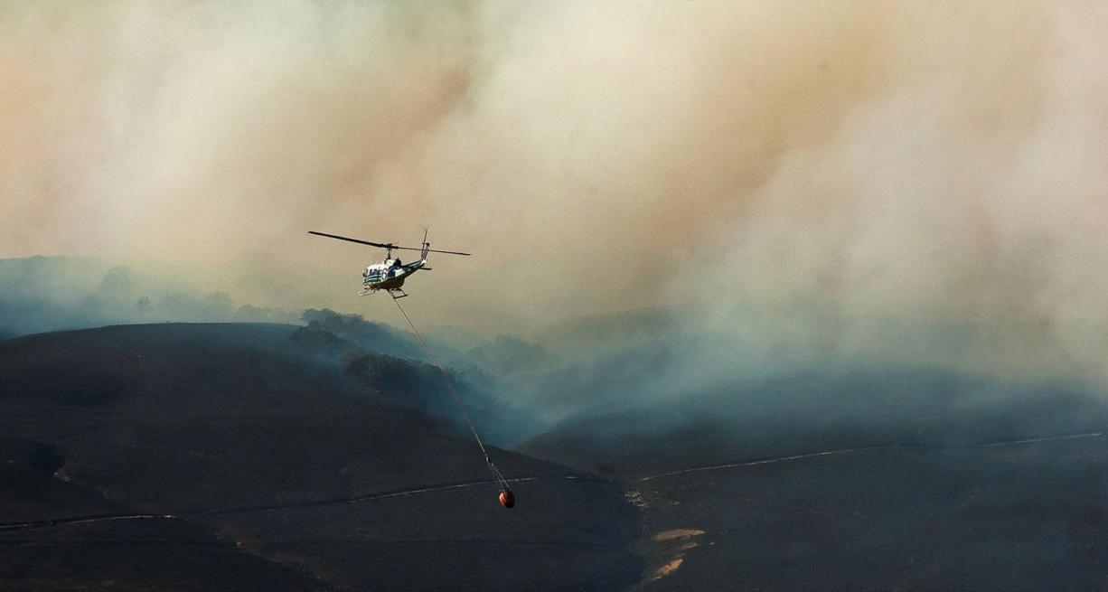 A helicopter drops water into a ravine just west of Chenowith Street as the fight to stop the Rowena Fire west of The Dalles, Ore., on Thursday.
