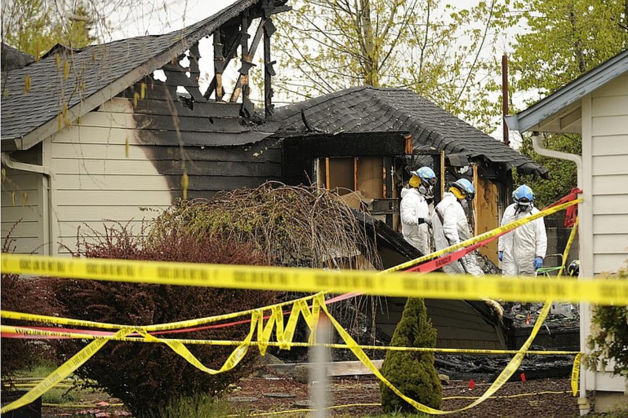 Investigators with the Vancouver Fire Arson Investigation Team and the Bureau of Alcohol, Tobacco, Firearms and Explosives study the burned remains of a fatal house fire on Northeast 13th Circle in Vancouver. Six people died in the Easter morning fire in 2011. (The Columbian)
