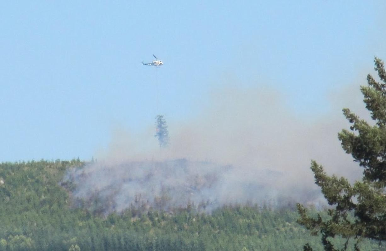 A helicopter makes a water drop on a wildfire burning Friday evening near the East Fork Lewis River near the mouth of Dole Valley in northeast Clark County.