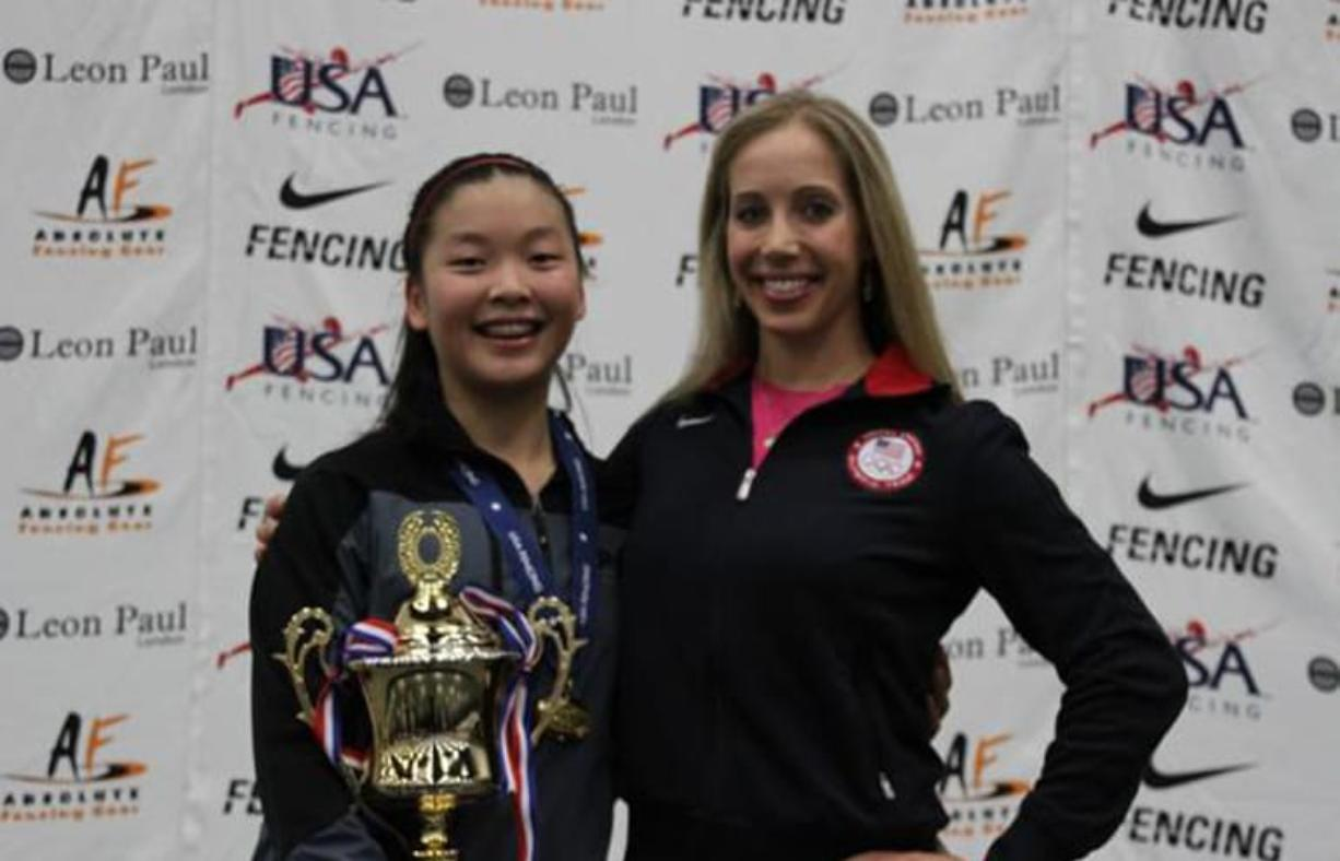 Malia Hee of Vancouver, left, received her gold medal from Olympic champion Mariel Zagunis after Friday's cadet women's sabre championship at the USA Fencing Junior Olympics.