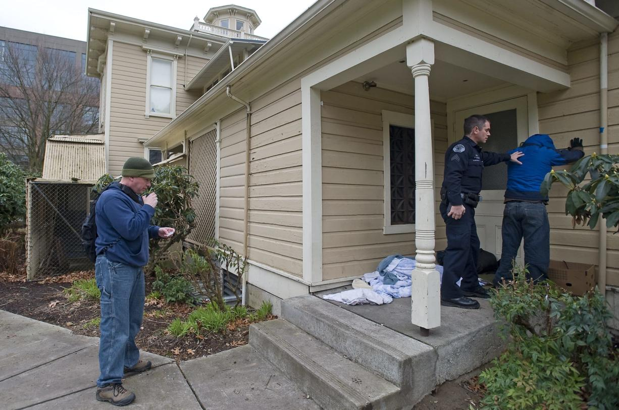 Vancouver Police Cpl. Drue Russell, left, runs a man's identification that he found camping next to the Slocum House in Esther Short Park while VPD Cpl. Duane Boynton secures the man after he disclosed to officers that he was carrying a knife, as part of an ongoing effort by authorities to make the park a safer place on Friday March 4, 2011.