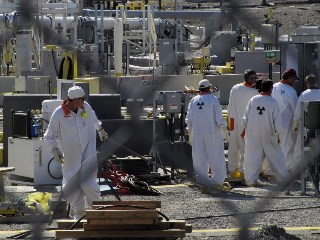 Technicians work at a Hanford nuclear reservation tank farm, where highly radioactive waste is stored underground, in July 2010.