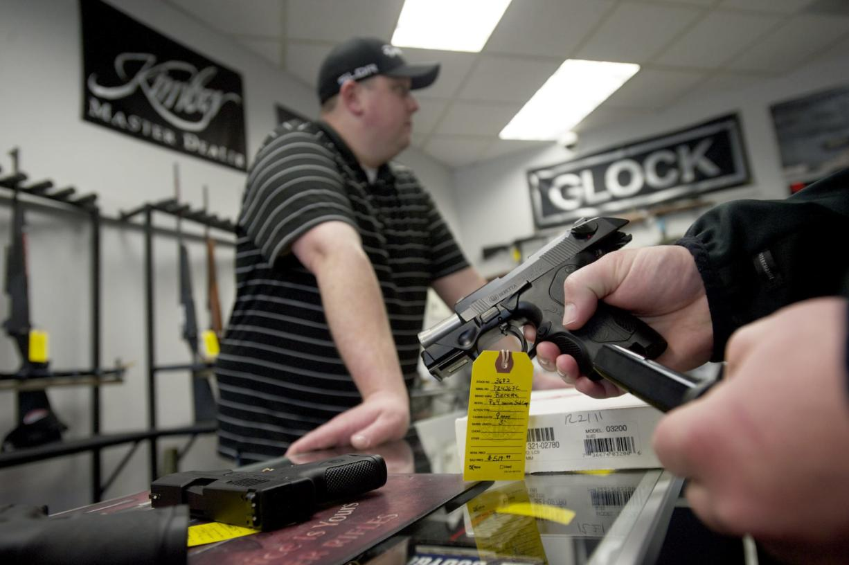 Brightwater Ventures Firearm Sales owner Nick Pratka waits as a customer looks at handguns.