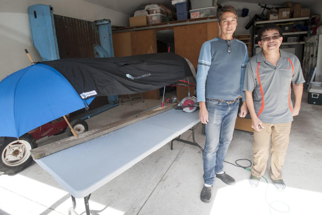 Chris Gibbons and Kevin Chong stand in front of one of their Slikr-Brellas at Gibbons' home in Vancouver. The men displayed their procut, a poncho that hooks over umbrellas to create a tent that can be used on the sidelines of sporting events, at the recent Wak, Roll 'n Run event in Portland, a fundraiser for United Cerebral Palsy of Oregon. They plan to put any profits from the sale of their product into a new non-profit to help disabled people learn about finance and business basics.