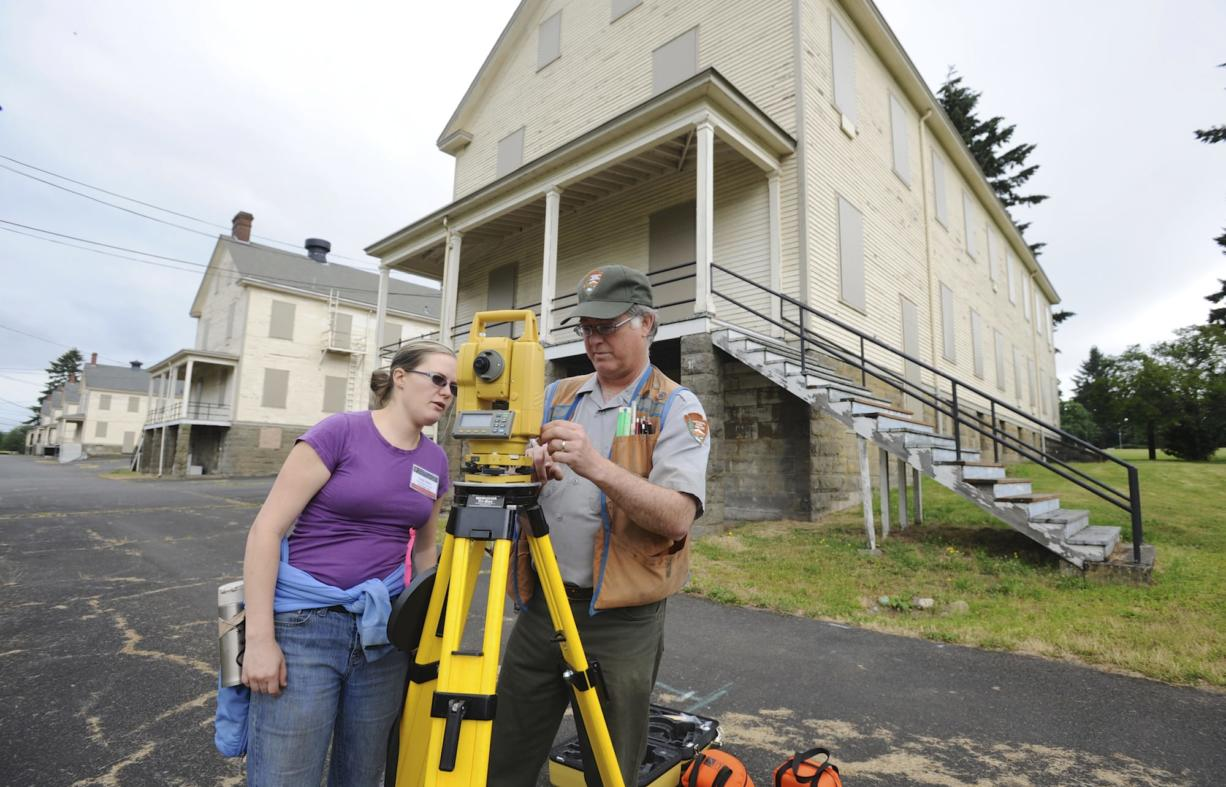 Graduate student Emily Taber and Doug Wilson, National Park Service archaeologist, use surveying equipment to set up a dig at the site of the 1854 Army flagstaff at Vancouver Barracks.