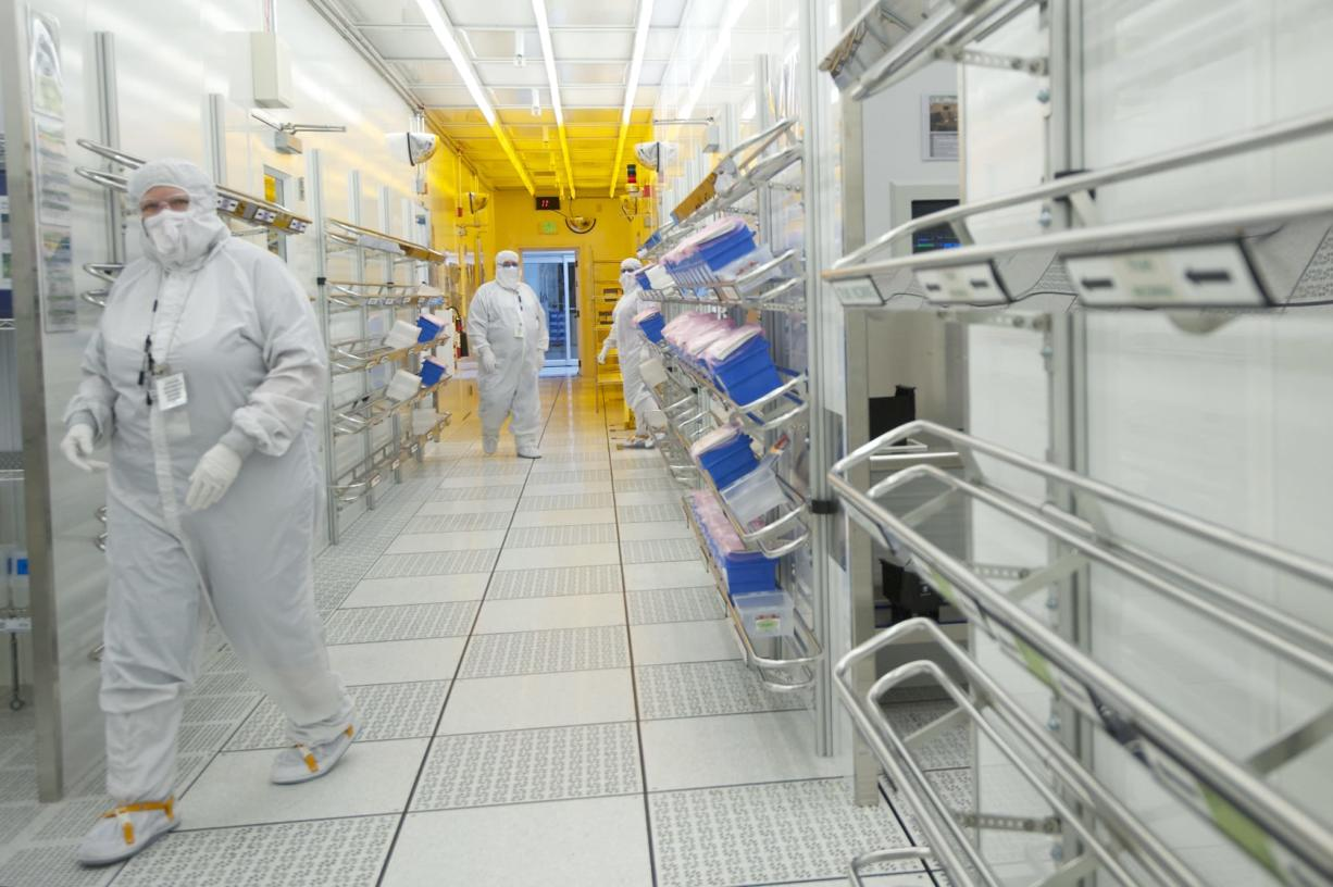 Linear Technology employees move through a corridor inside a clean room at the company's Camas manufacturing plant.