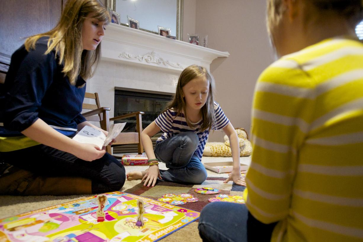 Kelly Slauson, 20, plays a game with Greta Brown, center, a child she cares for in Camas.