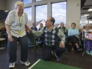 James Winther helps Liz Boss take aim as he leads teams of seniors in a game of bean bag baseball at Glenwood Place Senior Living in Vancouver earlier this month.