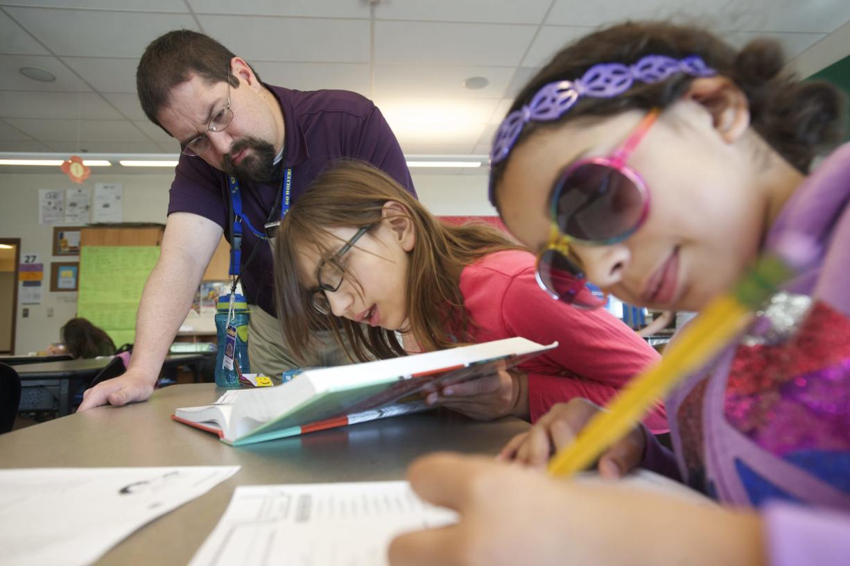 Substitute teacher and new WSUV graduate Bryan Moxley helps fifth-graders Anastazia McCusker, 11, center, and Monique Williams, 11, at Chief Umtuch Middle School in Battle Ground.