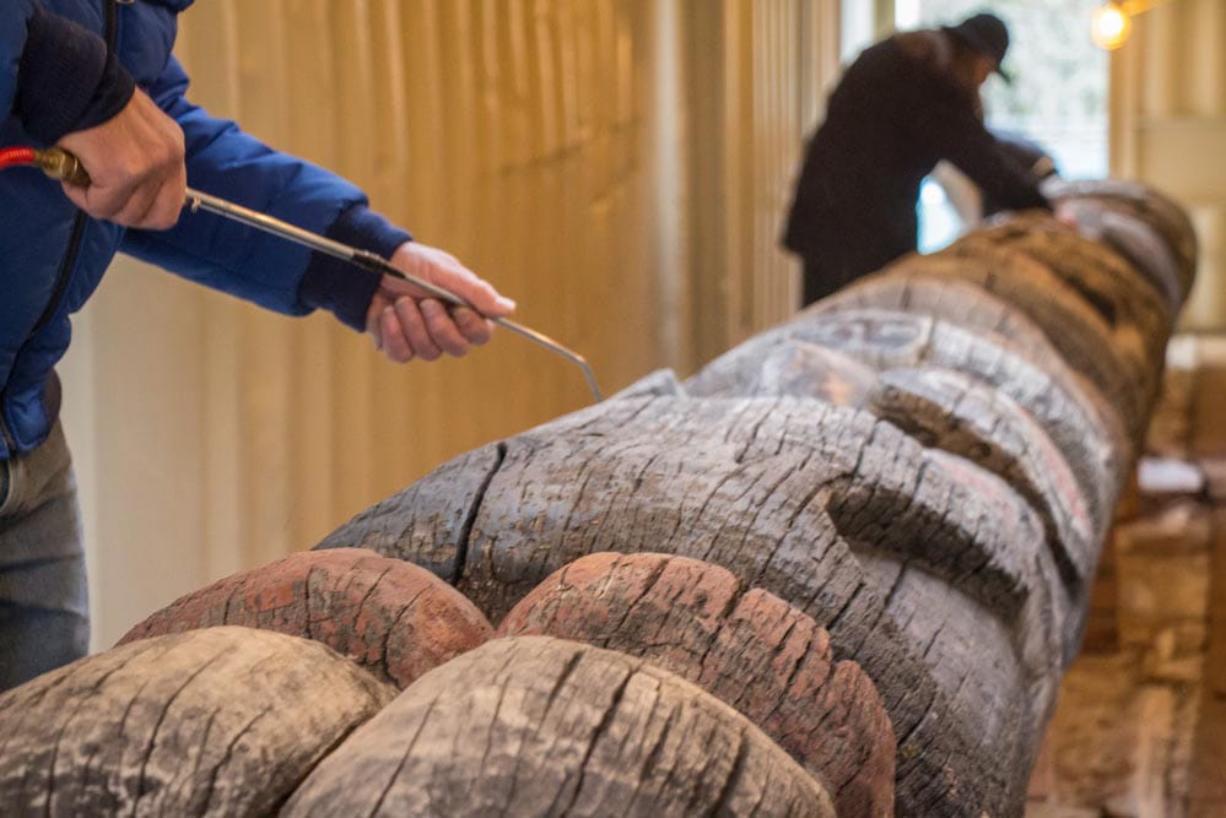 Volunteers work on the weathered Lelooska totem pole at the Oregon Zoo.