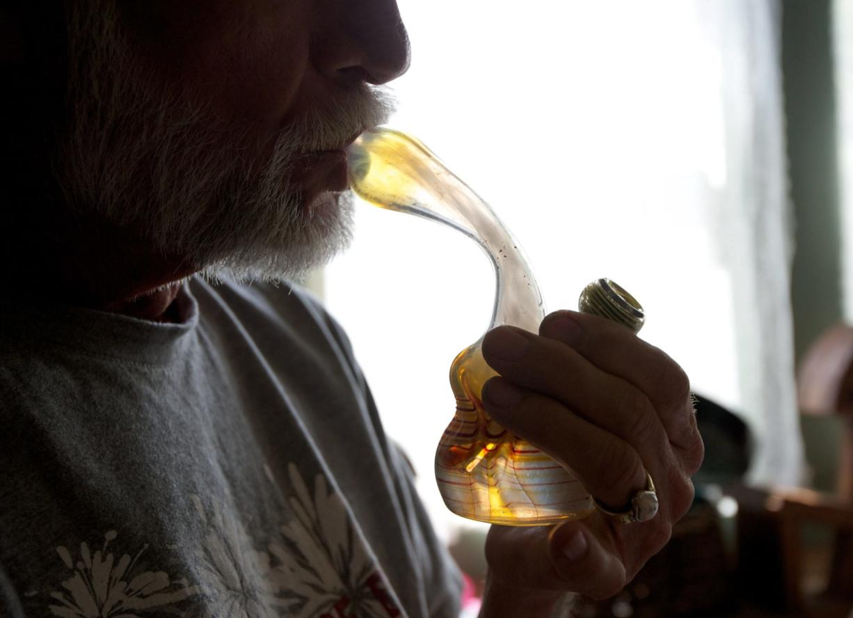 John, a 64-year-old chronic pain sufferer from Camas, smokes marijuana from a water pipe in his home Thursday.