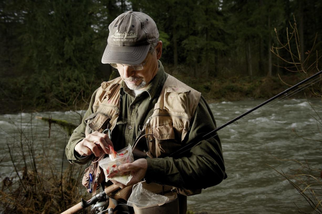 Lyle Cabe sorts through a plastic bag of spinners and spoons looking for the lure he wants while fishing for winter steelhead in the East Fork of the Lewis River.