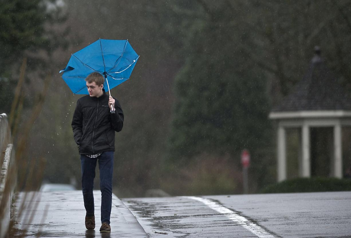 A gust of wind flips Spencer Henry's umbrella up as he walks west on Evergreen Boulevard over Interstate 5 on his way to work Tuesday. A continuing series of storms brought more than a half inch of additional rain, following an inch of rain that fell Monday. Wind gusts were measured as high as 28 mph at Pearson Field. Localized problems, such as flooded streets, were reported. Today's forecast calls for slightly less rain and wind.