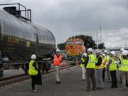 John Hack of Tesoro, second from left in orange vest, shares information about tank cars with invited guests at the Port of Vancouver's Terminal 5 on Thursday afternoon, Sept. 17, 2015.