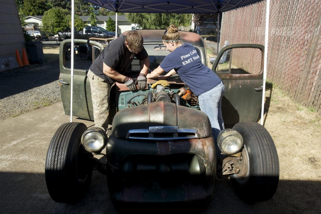 David Hubbard, left, and his wife, Jessica Hubbard, work on their Ford rat rod pickup at their home in Vancouver. Hubbard is expected to drive it 300 miles from St.