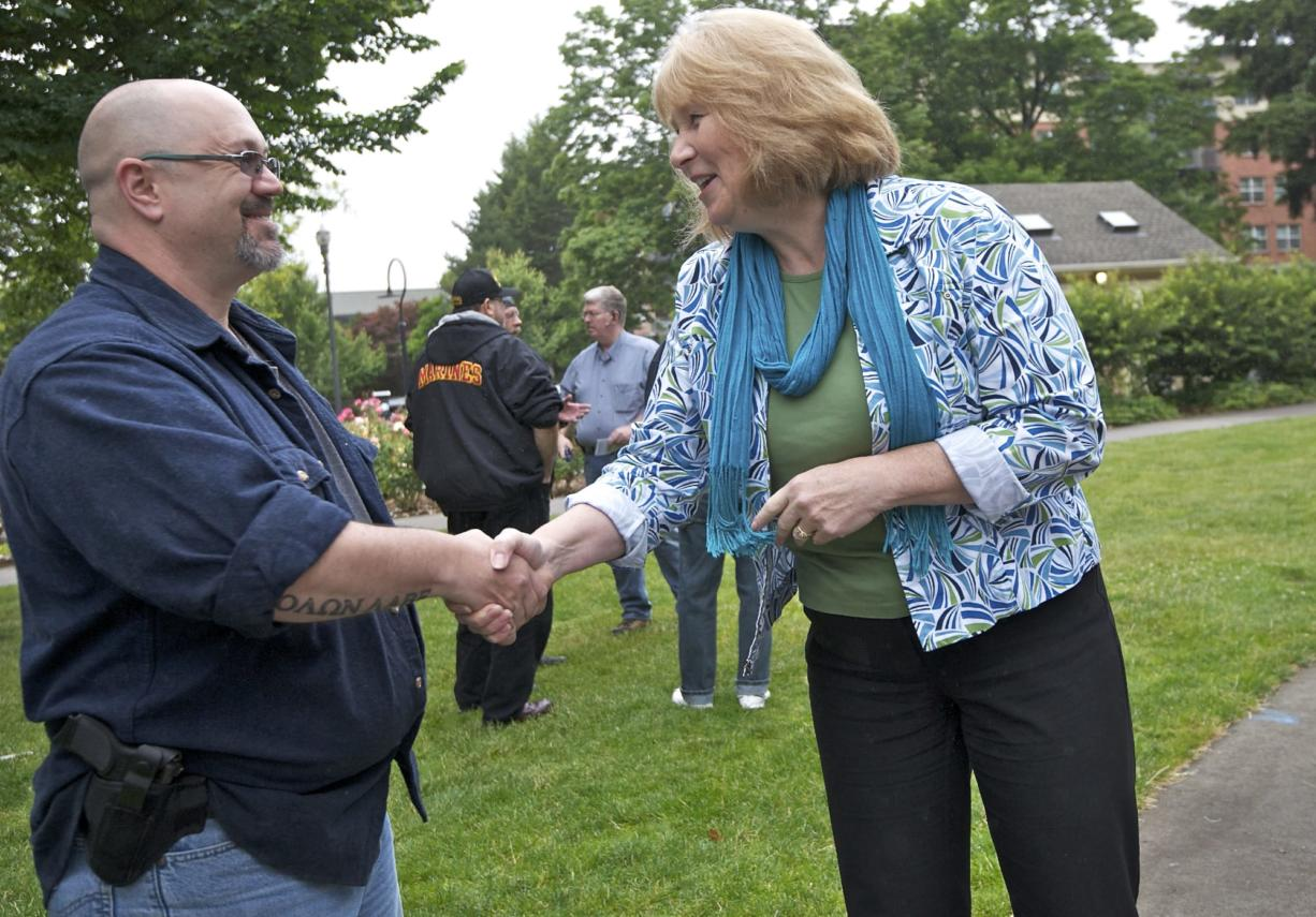 Open-carry gun activist Larry White and gun safety advocate and Vancouver City Councilwoman Anne McEnerny-Ogle shake hands as the two groups hold their separate rallies at Esther Short Park on Tuesday. McEnerny-Ogle was one of the few people who crossed camps to interact with the other group.