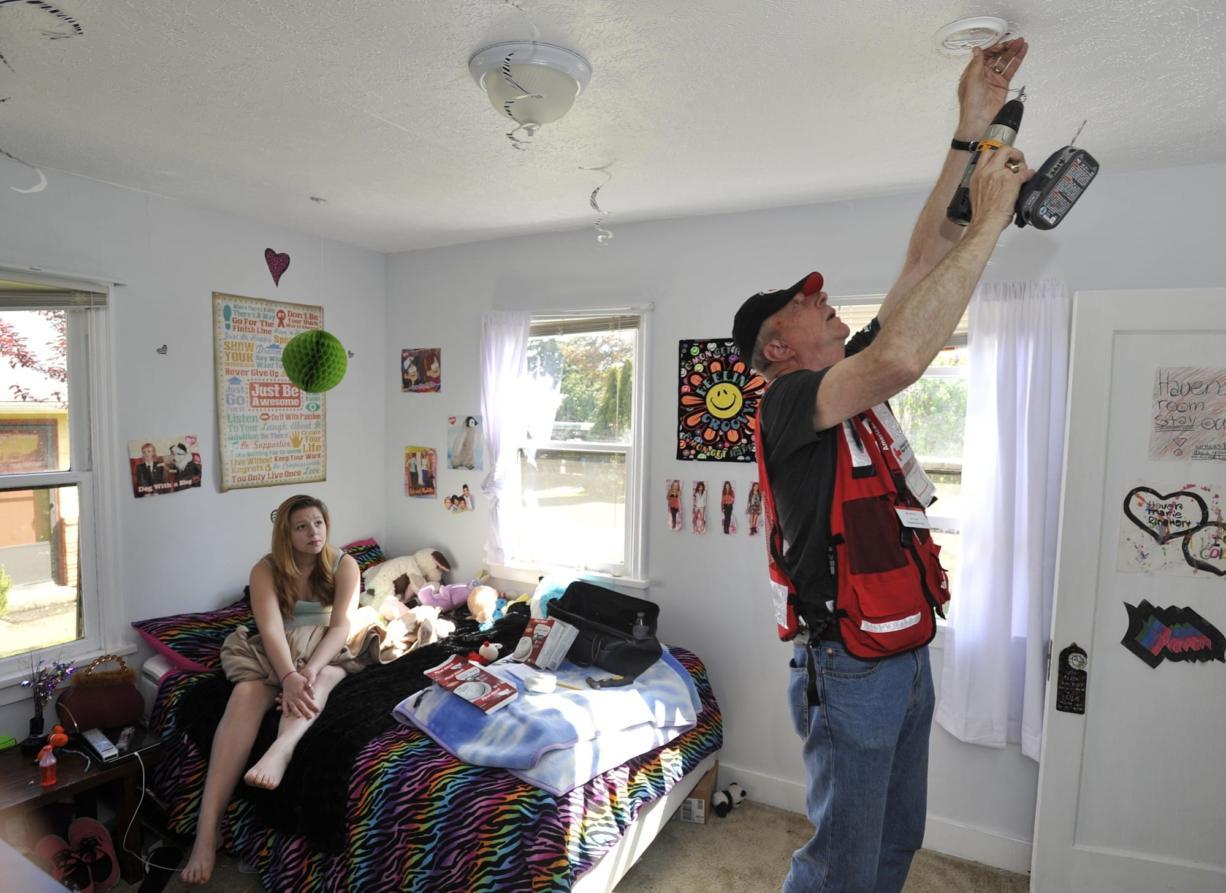 Red Cross volunteer Jeff Kuter installs a smoke alarm in Haven Reinhart's room Saturday.