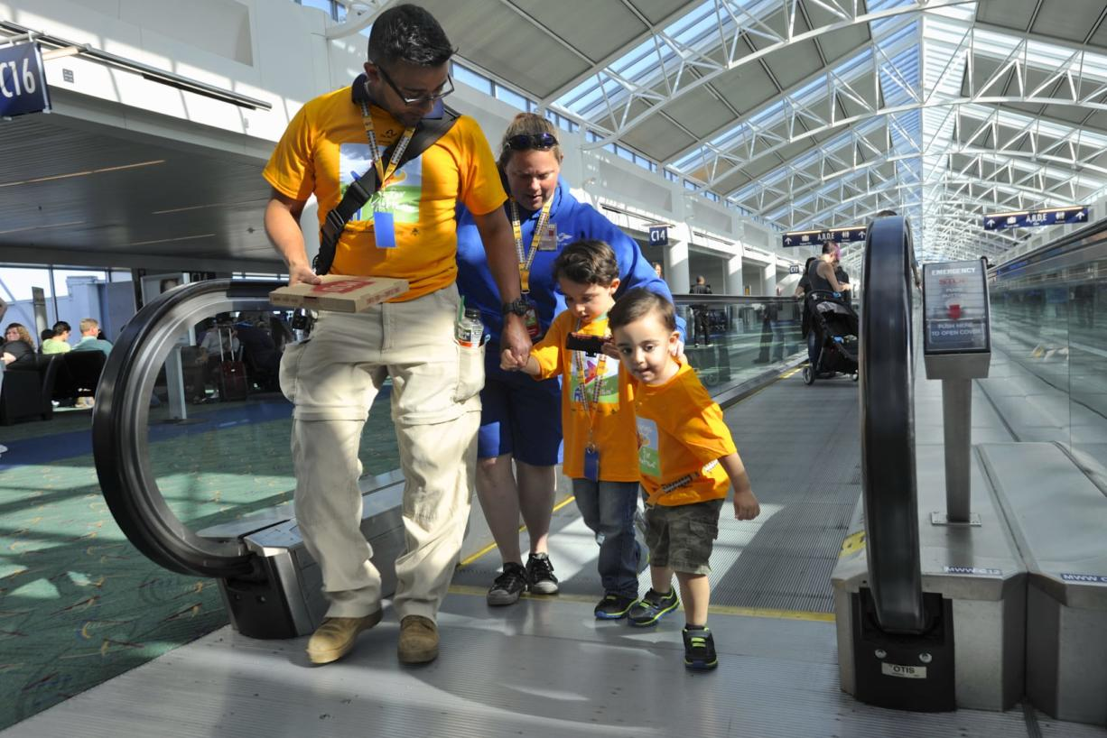 Saul Martinez Class, left, assists Owen Martinez with Catharine Hunter and Joshua Martinez, right, on the moving walkway at PDX at an event where families with children with autism could practice boarding a plane. (Greg Wahl-Stephens/for the Columbian)