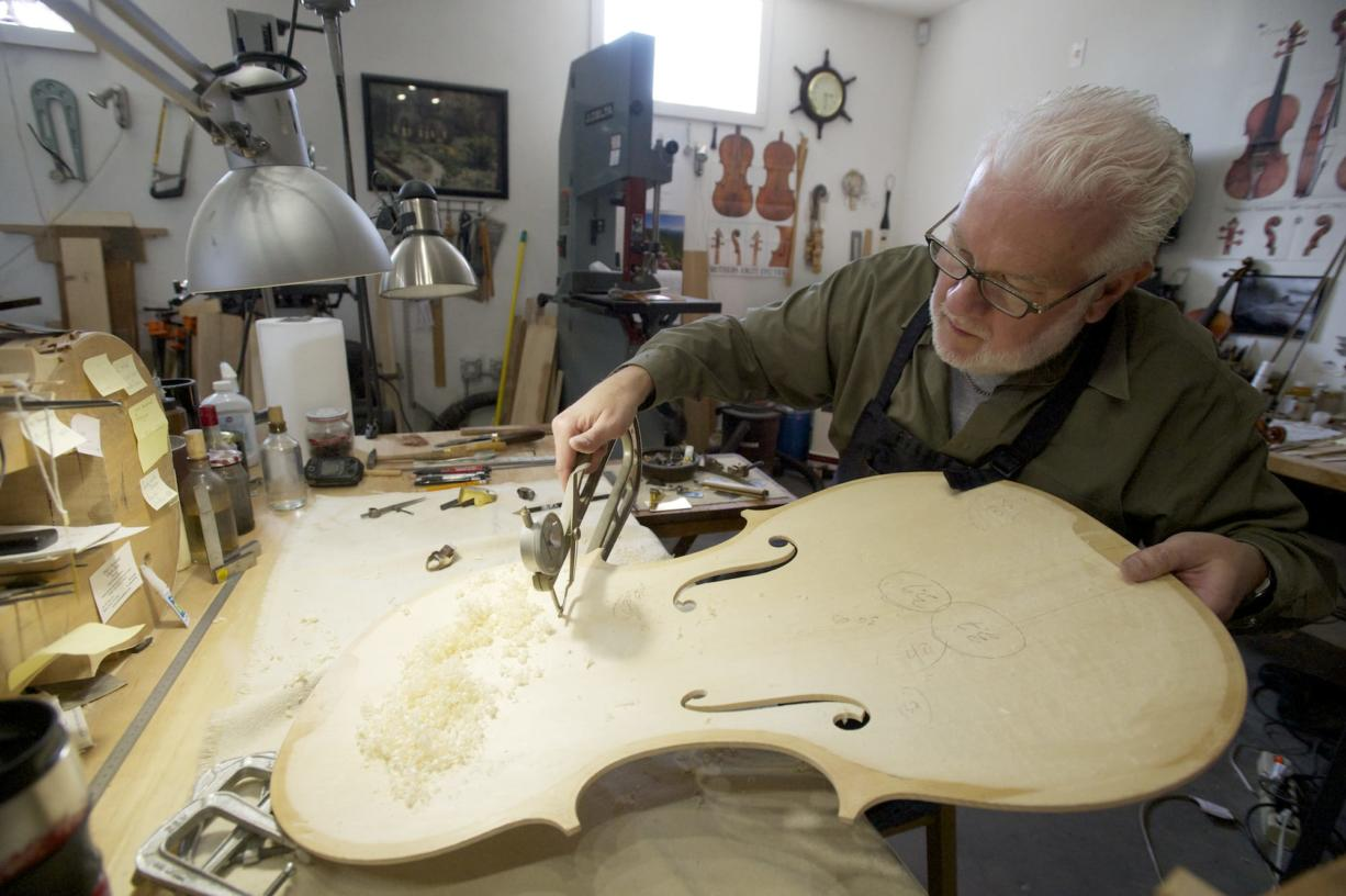Photos by Steven Lane/The Columbian Mark Moreland works on the body of a cello in his Battle Ground shop April 18.