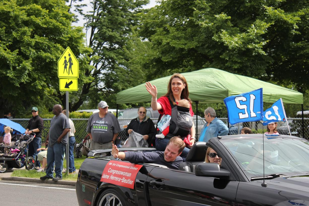 U.S. Rep. Jaime Herrera Beutler, R-Camas, waves to the crowd with her daughter, Abigail, in tow and her husband, Daniel Beutler, during a parade in Hazel Dell earlier this year.
