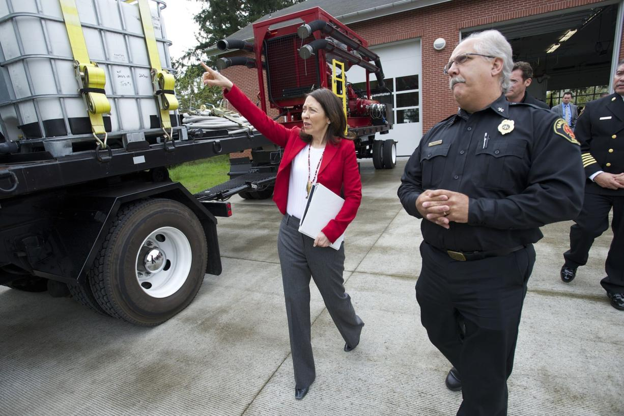 U.S. Sen. Maria Cantwell, D-Wash., walks past a firefighting rig with Vancouver Fire Department Division Chief Steve Eldred during a visit to Vancouver on Wednesday. Cantwell and local leaders highlighted the risks of crude oil being transported by rail.