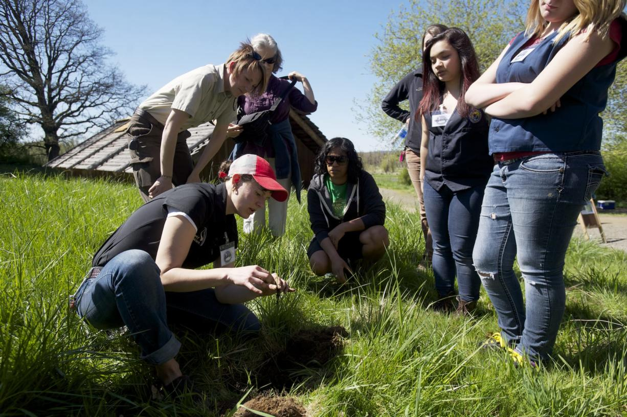 Sarah Hill, director of the Cathlapotle Plankhouse, left, shows volunteers how to plant camas during the plankhouse's spring opening celebration on Sunday at the Ridgefield Wildlife Refuge.