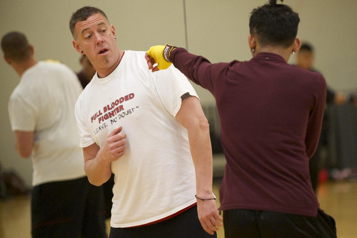 Tony Adams, founder of Mind Fitness Attitude Boxing instructs a boxing student during a Friday afternoon class at LA Fitness in Vancouver.