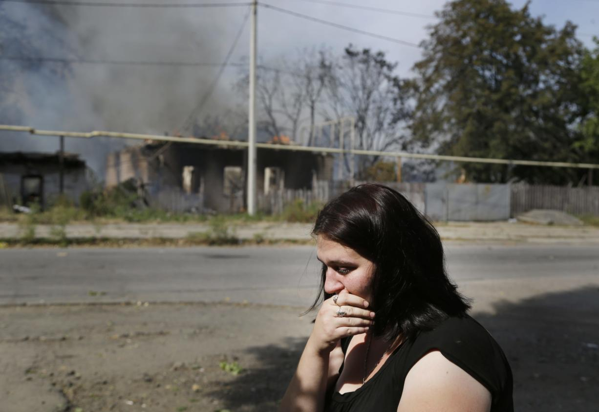 A local woman cries Sunday in front of her burning house after shelling in Donetsk, Ukraine.