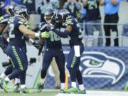 Seattle Seahawks Tyler Lockett, second from right, is greeted by teammates, including DeShawn Shead, right, after returning a Chicago Bears kickoff 105 yards for a touchdown to open the second half  Sunday, Sept. 27, 2015, in Seattle.