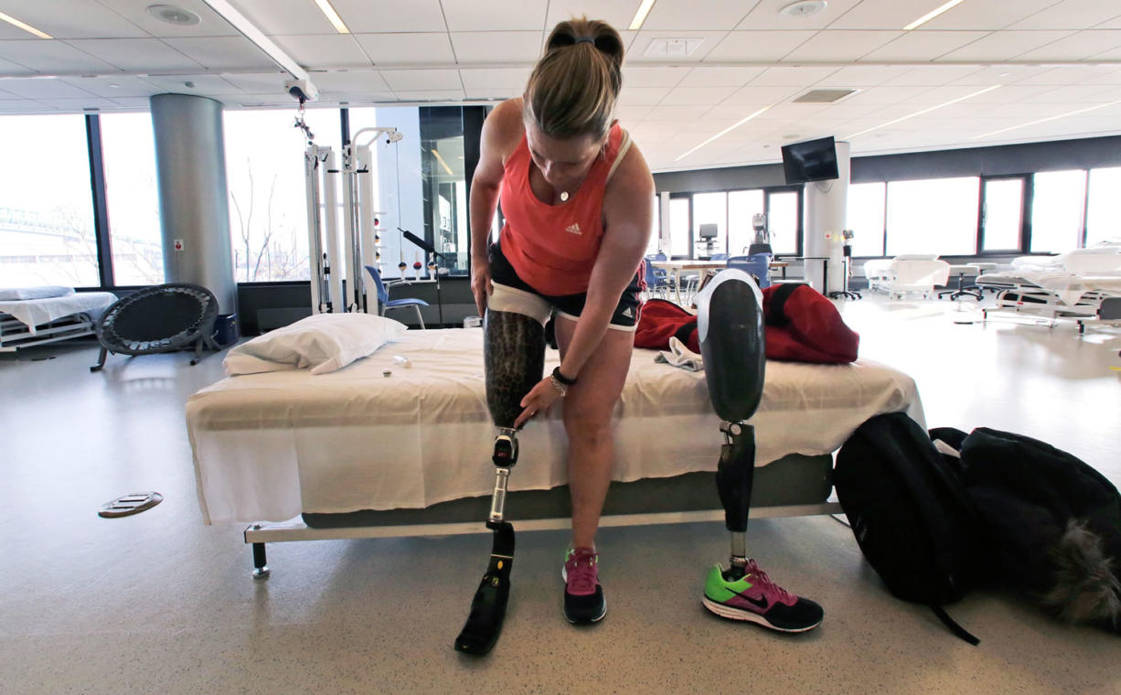 Photos by CHARLES KRUPA/Associated Press Boston Marathon bombing survivor Roseann Sdoia adjusts her running blade as she switches her prosthetic legs during a therapy session March 11 at the Spaulding Rehabilitation Hospital in Boston. Sdoia, a runner who did not take part in the last year's Boston Marathon, was in a crowd of fans near the finish line when one of two bombs went off nearby.