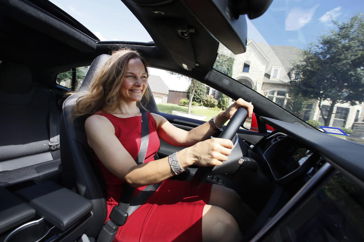 Elizabeth Farrell Peters drives her leather-free Tesla Model S, in Hurst, Texas. For car buyers like Peters and her husband Mark, who have been vegans for more than two decades, leather-free choices are limited. The car-buying site Edmunds.com says 78 percent of 2015 model-year vehicles have standard leather seats on at least one trim level. (AP Photo/Tony Gutierrez)