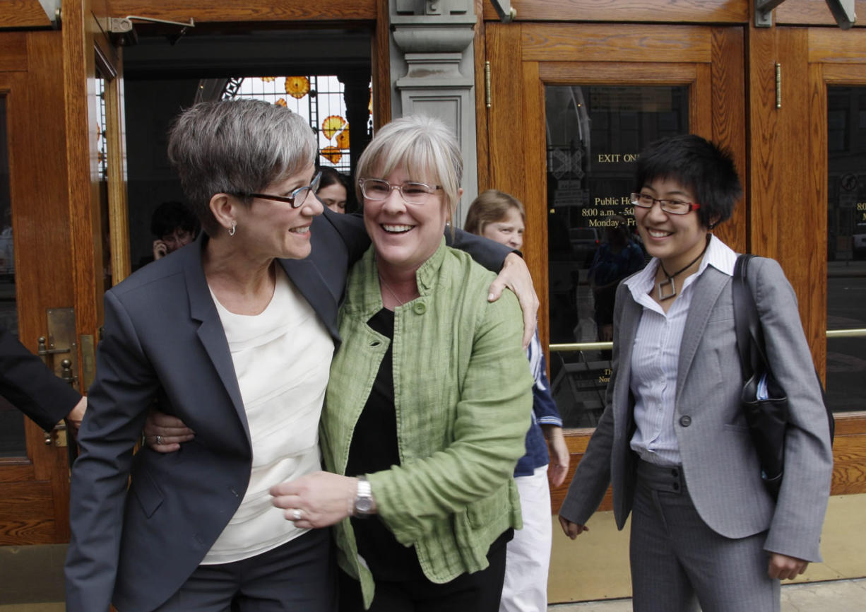 Sher Kung, right, a Seattle lawyer who worked with the ACLU, was killed in a bicycle accident Friday, Aug. 29, 2014.  In this photo taken Sept. 24, 2010, she looks on as Margaret Witt, center, and Witt's partner, Laurie McChesney, left, celebrate as they leave the federal courthouse in Tacoma, Wash.