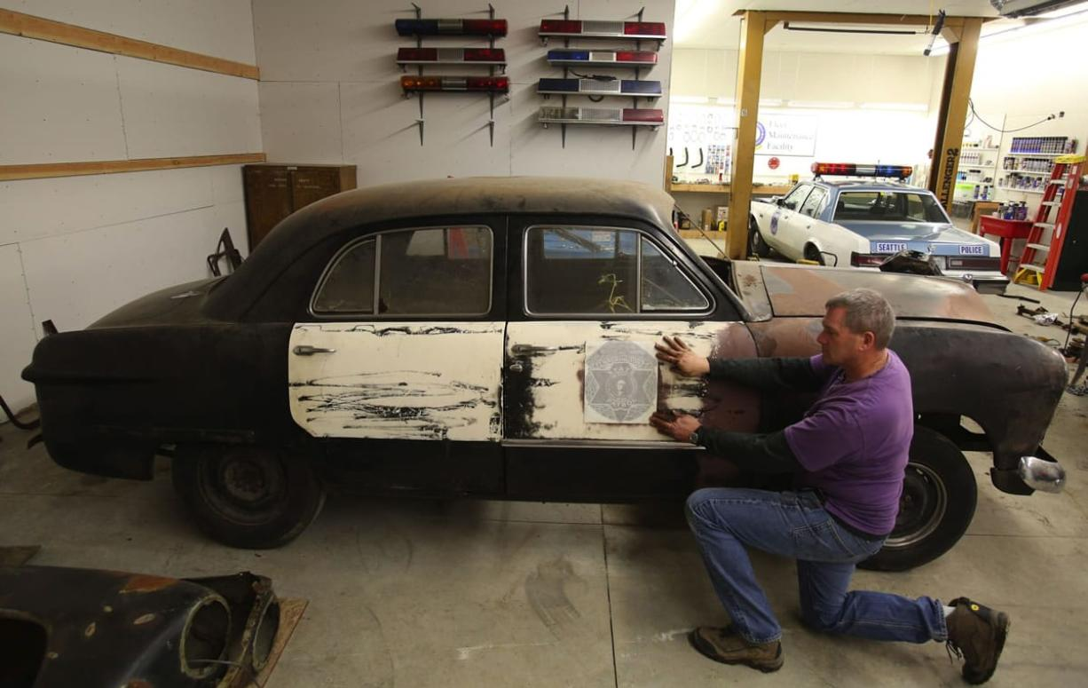 Seattle police Officer Jim Ritter of the Seattle Metropolitan Police Museum holds an original side-door decal that is being used in the restoration of a 1949 Washington State Patrol car.