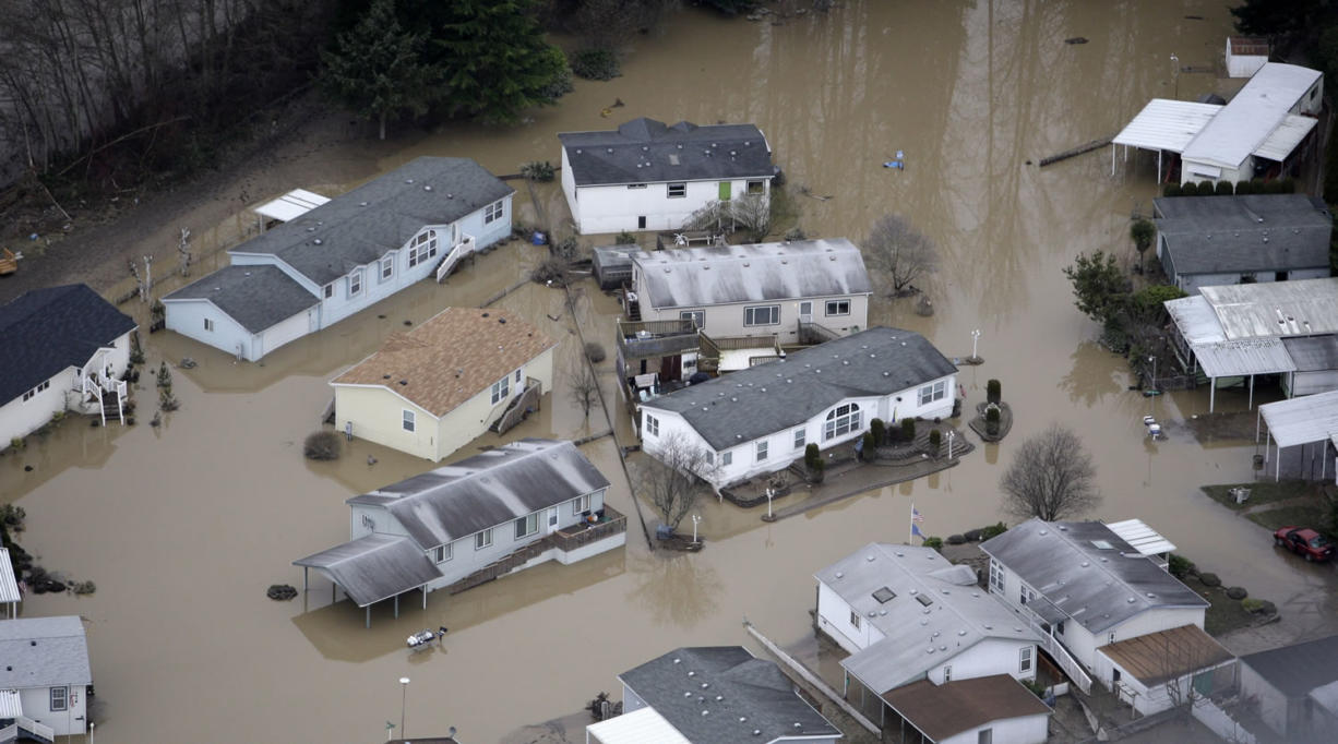 Flood waters surround homes in Orting in January 2009. As storms threaten to flood rivers throughout the Northwest again in late 2014, flood-control managers are increasingly turning to more natural approaches to keep rivers from overtopping.