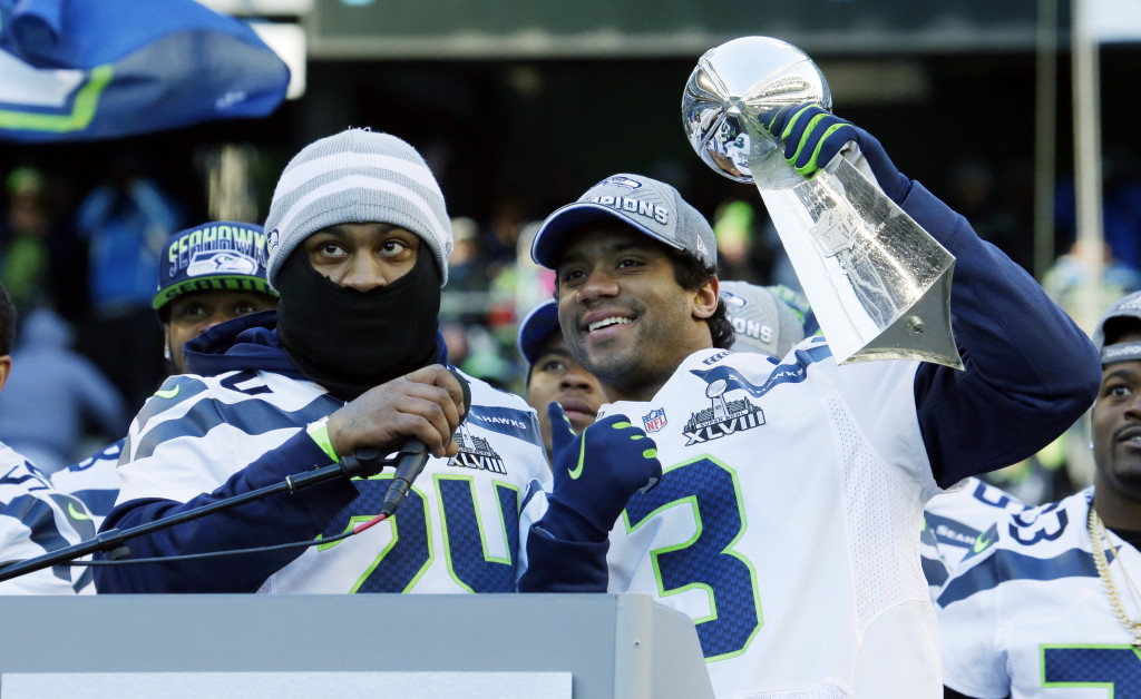 Seattle Seahawks Quarterback Russell Wilson Right Lifts The Vince Lombardi Trophy Next To