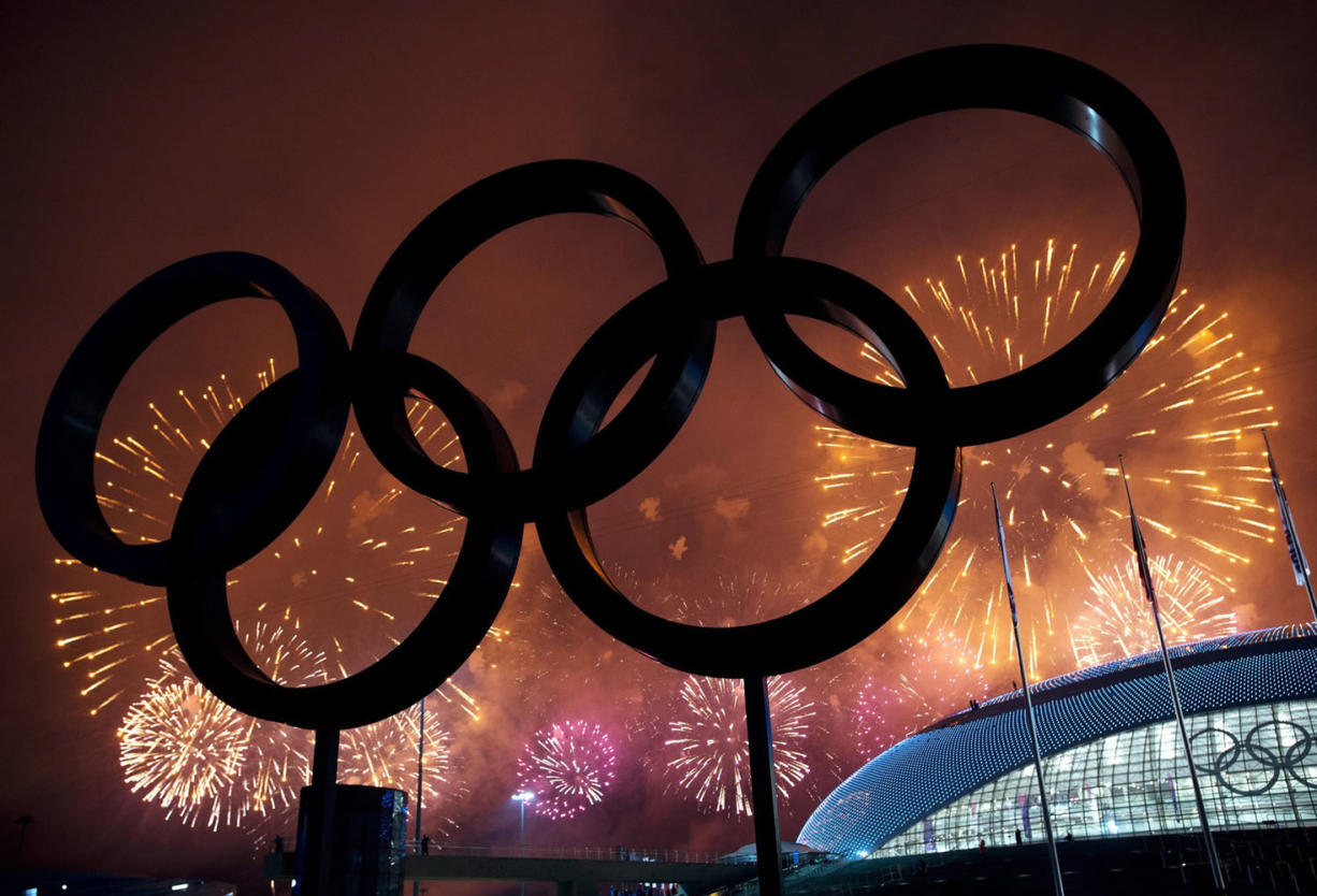 The Olympic Rings are silhouetted as fireworks light up the sky during the closing ceremonies at the 2014 Sochi Winter Olympics on Sunday in Sochi, Russia.