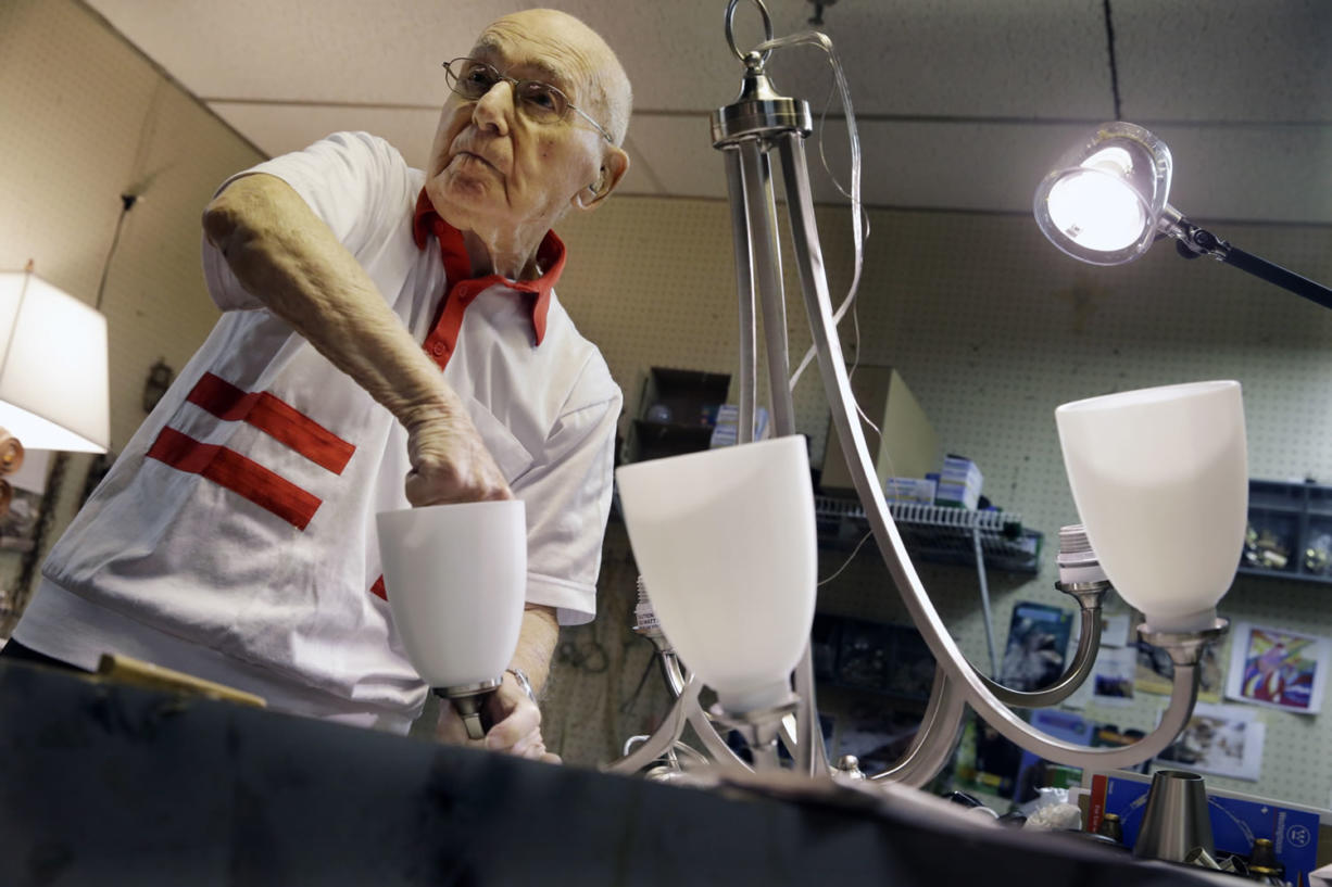 """Lighting repair specialist Herman """"Hy"""" Goldman, 101, refurbishes a light fixture in his workshop at Capitol Lighting where he has worked for 73 years on Monday in East Hanover, N.J."""