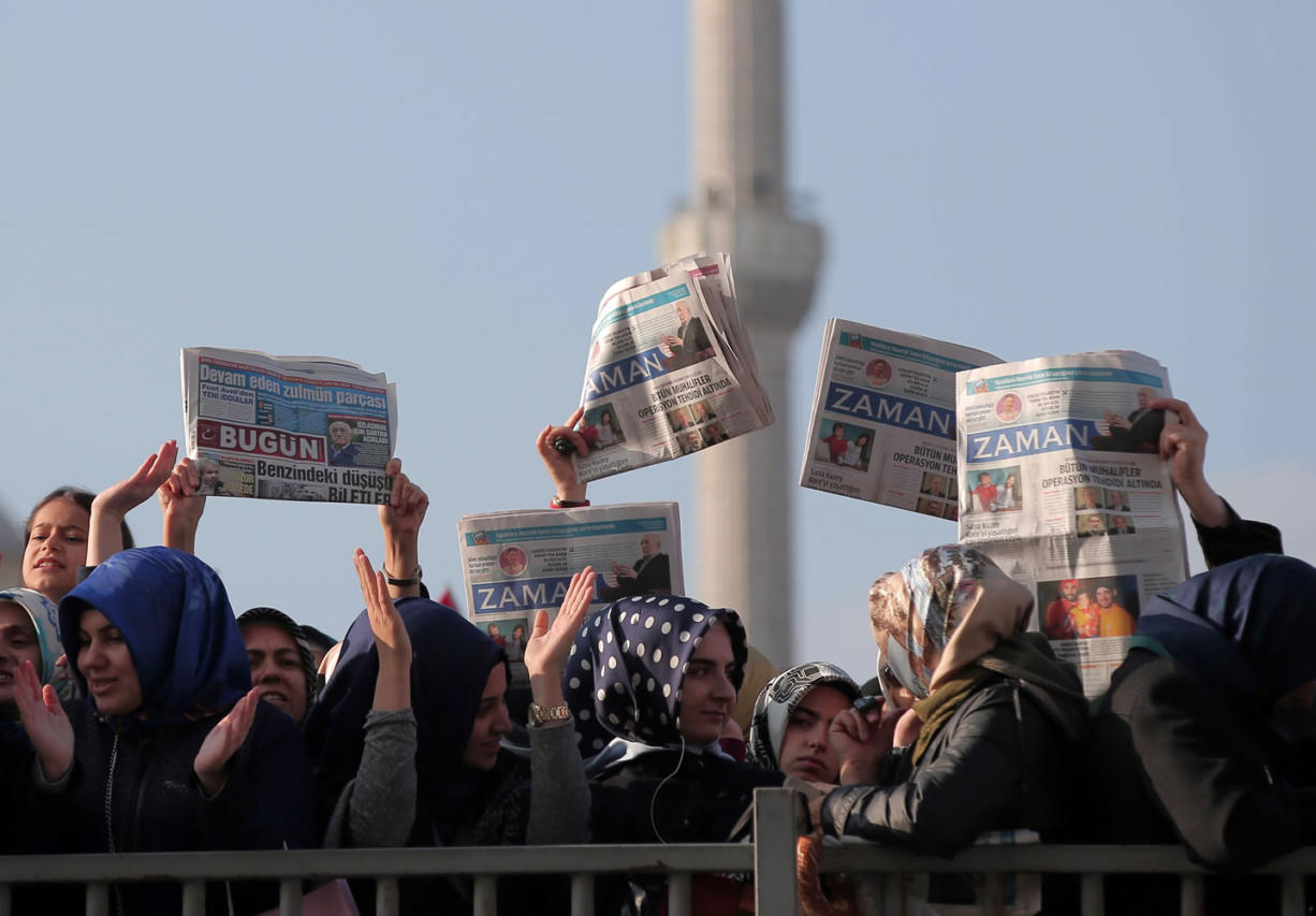 Women hold opposition newspapers as people gather Sunday outside the Justice Palace in Istanbul, Turkey, to protest against the latest detentions in Turkey.