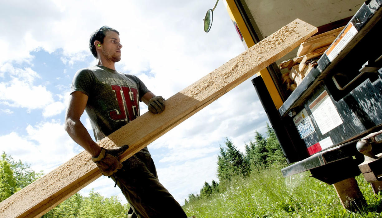 Alex Benson of the Idaho Department of Lands carries boards from trees that were planted 20 years ago to monitor growth characteristics and potential forest products markets. The boards were being cut June 20 at the University of Idaho Sandpoint Research Station in Sandpoint, Idaho.