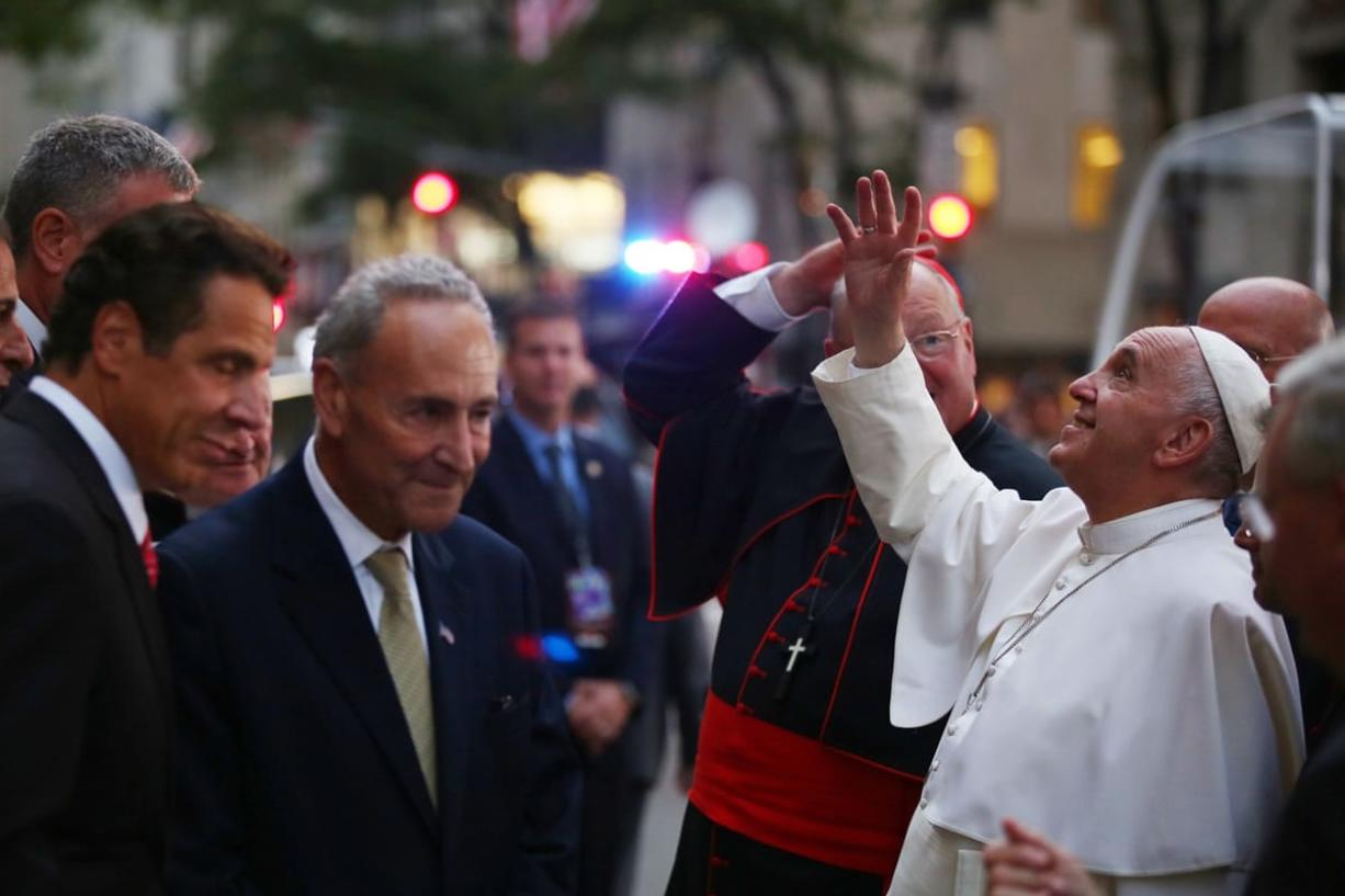Pope Francis waves to the crowd as he arrives at St. Patrick's Cathedral on Thursday in New York. New York Gov. Andrew Cuomo, left, and Sen. Chuck Schumer, D-NY, wait to greet the pope. (Damon Winter/The New York Times via AP, Pool)