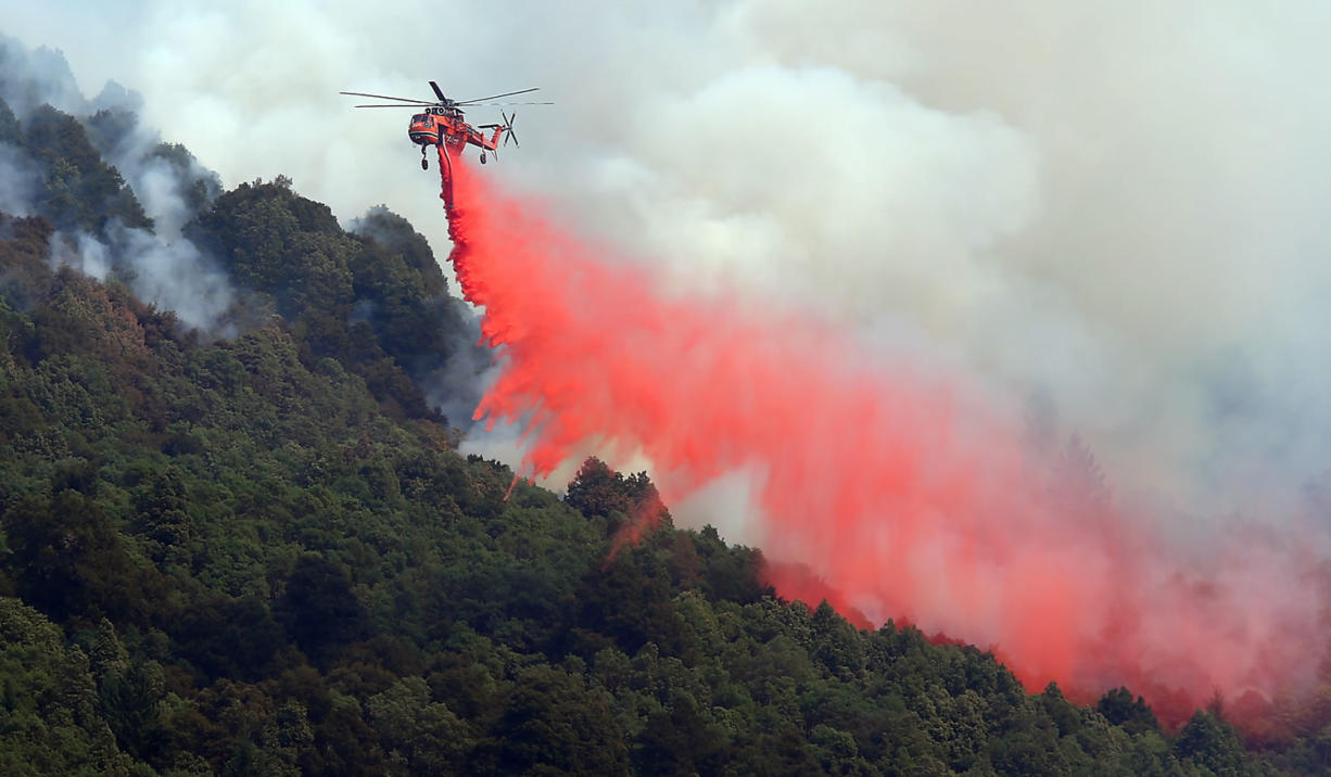 A helicopter drops retardant on an area on the northern end of the Lodge Complex Fire, near Leggett, Calif., on Monday.