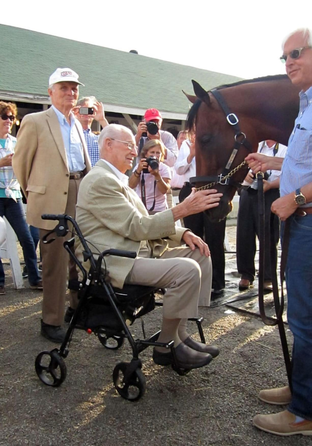 William McGee, 98, who has seen six Triple Crown winners, pats American Pharoah in June. The 2015 Triple Crown winner is scheduled to make the last start of his racing career on Saturday. As a boy, McGee attended what then was Shumway Junior High in Vancouver. (Gary B.