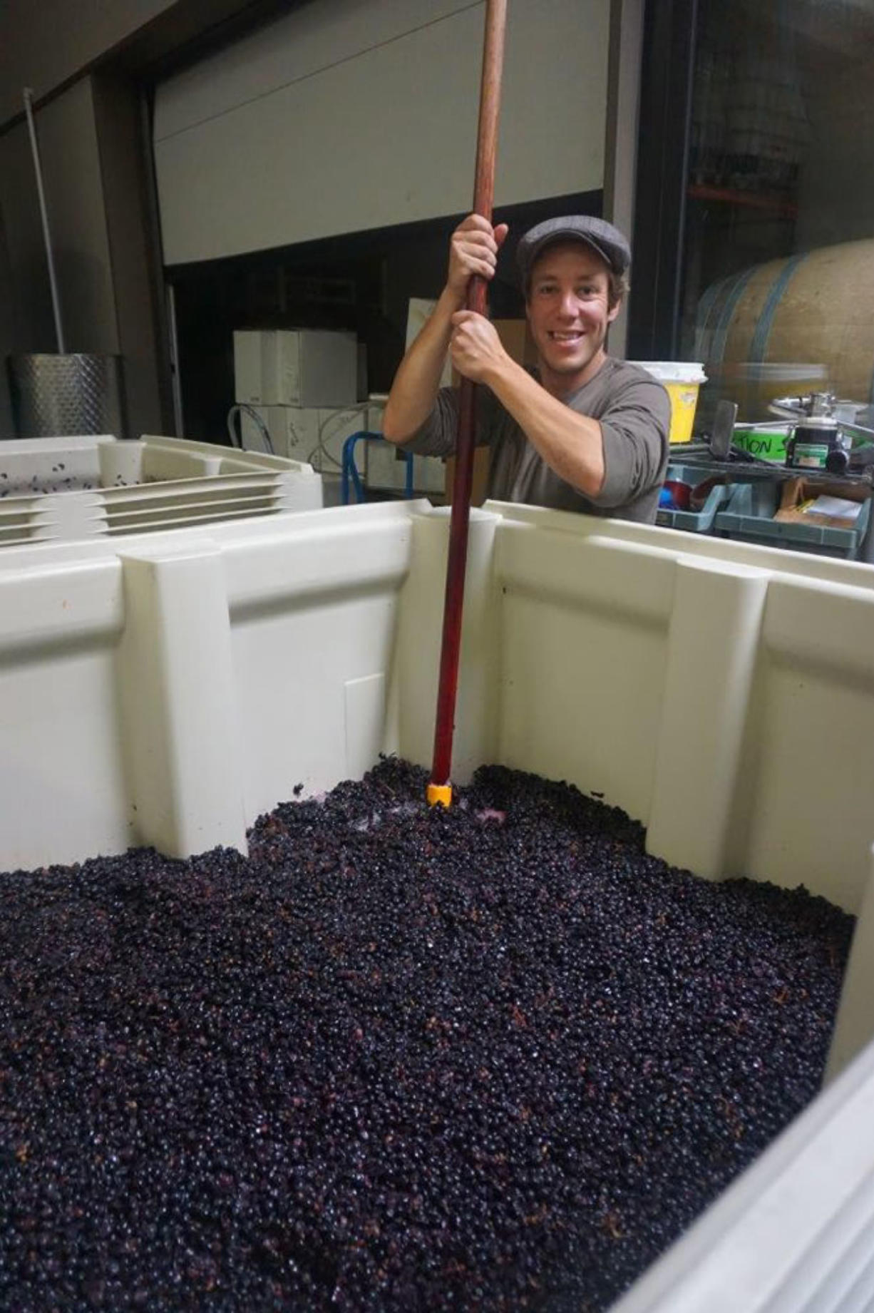 Working with Division Winemaking Company since its inception, French native Aurelian punches down grapes on the production floor at Southeast Wine Collective in Portland.