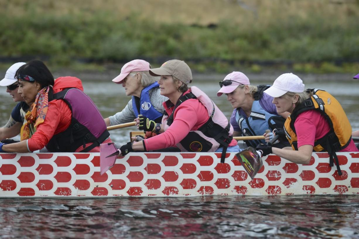 Mary Sullivan, center in orange life jacket, paddles with the Pink Phoenix dragon boat team at a practice on the Willamette River. Like the rest of the team, Sullivan and her twin, Meg Perlick (shown below on the left in purple T-shirt), are breast cancer survivors.