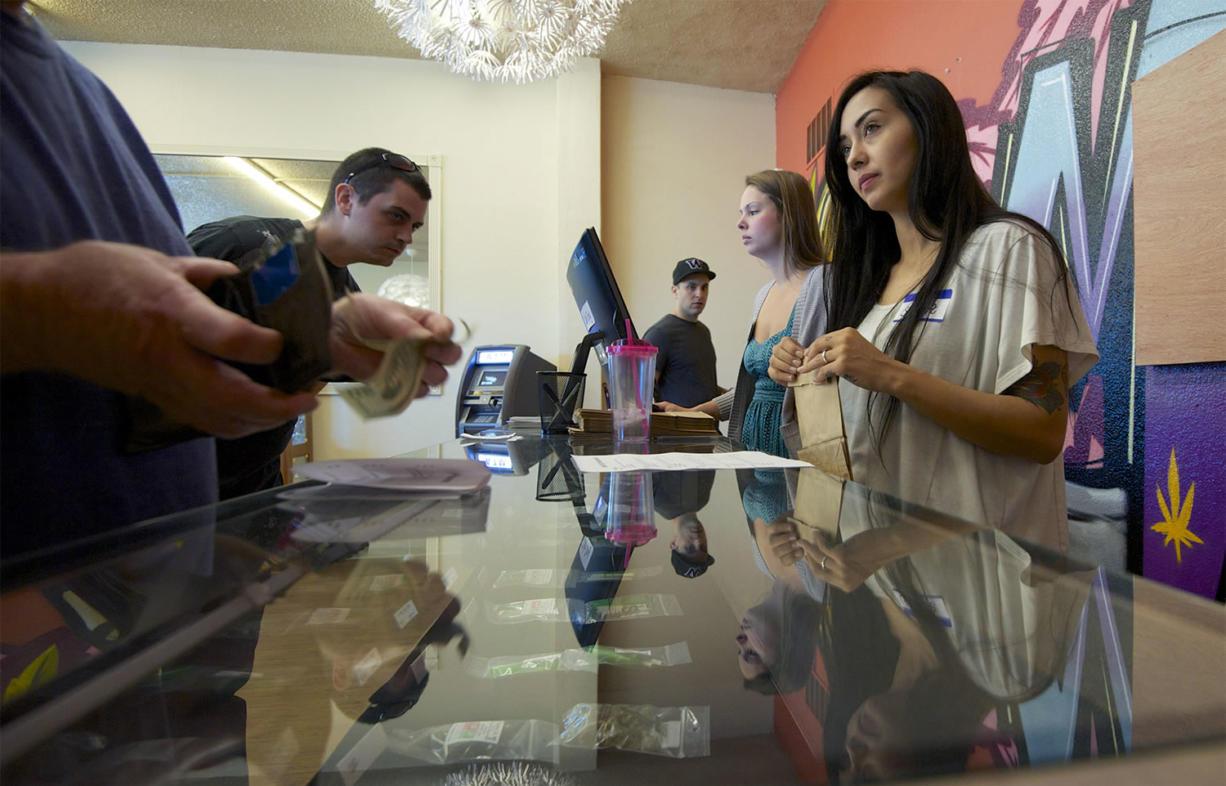 Main Street Marijuana clerk Sara Kemple, right, 25, helps customers at the store.