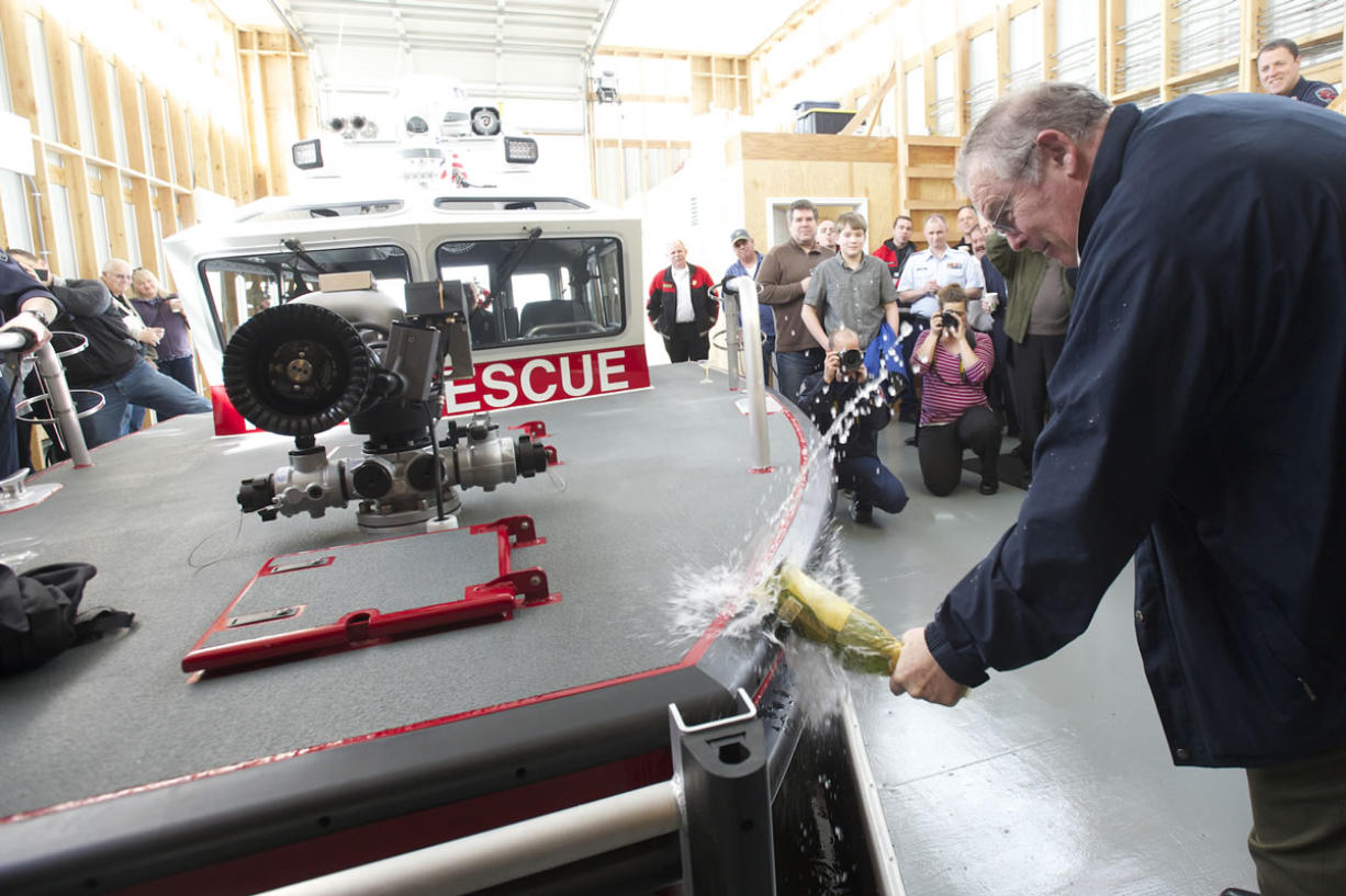 Bruce Firstenburg christens Clark County Fire & Rescue's new boat during a ceremony at the Ridgefield Marina on Friday. The boat is named after his mother, the late Mary Firstenburg.